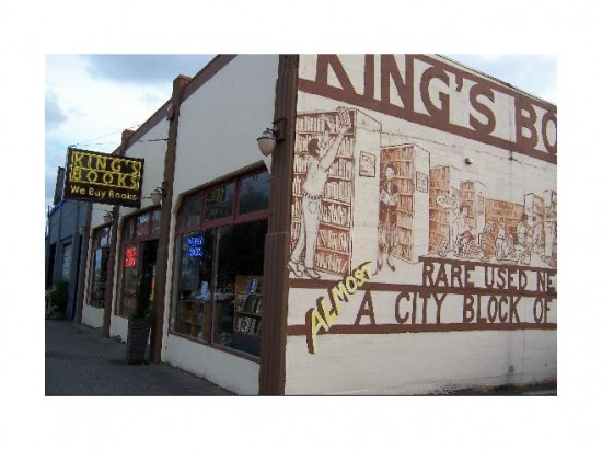 The picture is taken as a corner shot of a beige building with maroon trim. A mural on the side wall reads King's Books. Rare Used New. Almost A City Block of Books.
