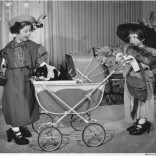 "In this 1951 photo, Kathy Link and Mary Lynn Martin play make-believe, dressing up in grown-up clothes and recruiting a docile cat to play the part of baby. With over-sized gloves, Kathy demurely takes the helm of the pram, while Mary Lynn reacts with the surprise warranted by her discovery. ""He has so much hair!"""