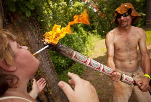 A woman lights a cigarette from a man using a blow torch covered with Budweiser cans during the 2012 Red Neck Summer Games in Dublin, Georgia. Richard Ellis/Startraksphoto.com
