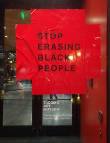 "Protesters placed large stickers stating ""stop erasing black people"" on the doors of the Tacoma Art Museum."